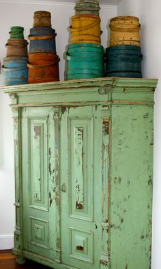 green cabinet with colorful firkins