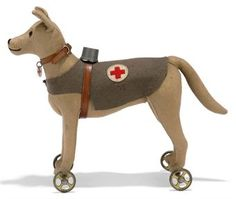 A STEIFF FIRST AID DOG, (1122d), light brown felt, brown and black glass eyes, black stitching, grey felt coat with Red Cross symbol, leather collar with Red Cross tag and harness with wooden container, gold painted cast metal wheels and FF button with remains of white tag, circa 1915-17 --9½in. (24cm.) long (slightly faded)