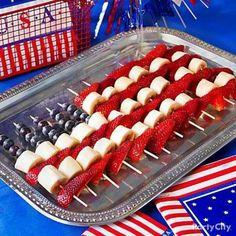 Create an American flag using bananas, strawberries and blueberries on kabob skewers