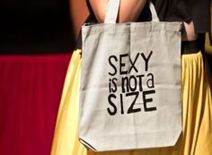 """A model carries a tote bag emblazoned with the words """"Sexy is not a size"""" in the Hannah Olson for Hannah Caroline Couture show during Omaha Fashion Week's Ready to Wear 1 Showcase on Aug. 19, 2014. By: REBECCA S. GRATZ/THE WORLD-HERALD"""