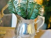 We love this great way to use family heirlooms. Pull out vintage silver  pieces, like this creamer, and tuck fresh evergreen into them to create  mini holiday arrangements.