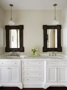 Dark mirror frames with white cabinets.
