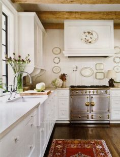Vintage all white kitchen, apron front farmhouse sink, antique stove, vintage plates, gorgeous wood floors & beams, BIG window