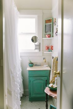 The green vanity makes this tiny bathroom in Oakland, California, bright and happy.