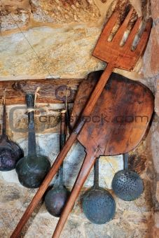 traditional oven and cooking utensils arranged against a stone wall