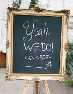Gold framed chalkboard on gold easel as wedding sign.
