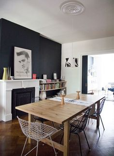 A black wall adds drama to this dining room with a natural wood dining table with mid-century dining chairs in black and white