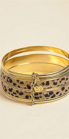 This bracelet features a cluster of 2 printed leopard and 3 gold stacked bangles with gold chain link and charm detail.
