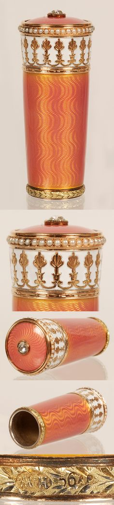 A Faberge chased gold, gem-set, and guilloche enamel parasol handle, workmaster Henrik Wigstrom, St Petersburg, circa 1903-1908. The two-color enamel cylindrical handle with tapering sides decorated in vibrant translucent salmon color enamel over a wavy engine-turned ground with a band of white opaque enamel against a raised palmate border beneath a seed pearl band, and a bezel-set mine-cut center diamond.