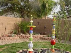 """""""Polatems""""  birdbaths, bird feeders and planters.  collect beautiful pots and plates dig a hole 12"""" deep insert a piece of rebar,  Fill the hole with concrete. Level the rebar to make it straight. let dry overnight. start putting the pots and plates onto the rebar in an artistic order, gluing them as you go..use glass glue.. Soo going to try this!"""
