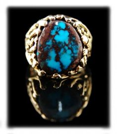 An outrageous Bisbee Turquoise Men's Gold Ring created by John Hartman of Durango Silver Company located in Durango, Colorado USA.  Bisbee Turquoise is admired worldwide and it is known by Turquoise collectors to be the king of all of the Turquoise types on earth. Mining of Bisbee Turquoise ceased over 35 years ago so it has become very scarce and rare! Bisbee Turquoise is among the most valuable Turquoise in the world.  Click on the photo to view additional photos and information.