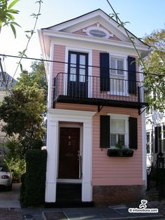 Pink house with white trim and black shutters. Charleston