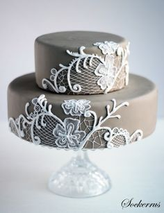 The white lace design on this wedding cake stands out nicely against the pale (brown?) fondant.