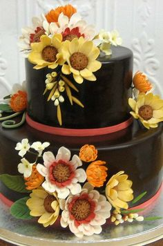 Edible sugar flowers tumble down the sides of this dark brown cake with coral accents, by Cheryl Kleinman Cakes. #wedding #cake