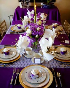 Pretty purple table decor... fun place settings! table decor same for large table under bubble chandelier and for small table in middle section of studio. Place settings only on small table. Wine glasses for tasting on large table.