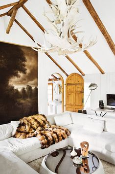 This Amazing Home is a Lesson in Sophisticated Décor// Fur blanket, antler chandelier, wood beam ceiling, round door