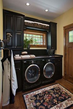 Laundry room with dark cabinets and washer/dryer