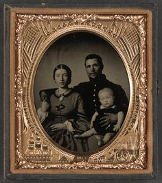 A lovely photo of an unidentified soldier, wife and child. Both wife and husband wear a hint of a smile. Look closely at their clasped hands over her shoulder and you will see it appears they have traded rings. She wears a large band on her right index finger, and he wears a small band on the little finger of his left hand.
