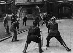 Staff, wearing gas masks, play cricket outside Chancery Lane offices in London during the Blitz, 1940s