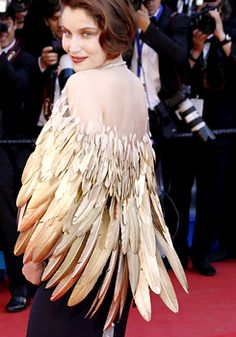 Erik Halley's unusual transparent hook gold-feathered cape - worn over a navy Dior Couture gown  on Laetitia Casta, Cannes Film Festival (May 26, 2013)