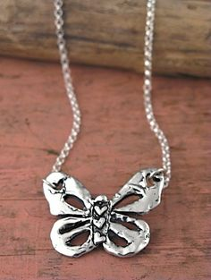 "This playful butterfly by Island Cowgirl dances among silver links. The words ""fly high"" engraved on the back remind you to always reach for the stars. Three little heart can symbolize so much... love, family members or best friends.  18"" length/pendant 1"" tall by 1 1/2"" wide. $84 at Quirks of Art."