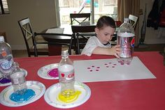 "I gathered up several different sized soda and sparkling water bottles, making sure to choose only the ones that have the ""flower"" shaped bottoms. Set out a few plates of tempera paint and let the kiddos start stamping!"