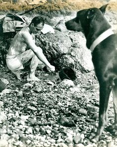 """Private First Class Fred Muscard and """"Lux"""", Okinawa, April 1945 by Marine Corps Archives & Special Collections, via Flickr. The caption on this photograph reads """"Knight of the Bath-His rifle in easy reach and his constant companion on the alert, Marine Private First Class Fred Muscard of Springfield, Mass., lathers up for a once over at Motobu Beach, Okinawa. The Doberman-Pinscher """"Lux"""", and his handler are members of a Marine Corps War Dog Platoon."""""""
