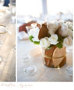 Simply elegant ... rose buds, a bit of greenery, and matched brown leaves in a simple glass container as centerpiece.