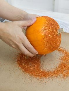 Spray the top and middle portion of a pumpkin with spray adhesive. While the glue is still wet, use a spoon to sprinkle glitter over the sticky surface of the pumpkin. Allow to dry.    Tip: Unless you want to glitter the stem, try not to spray it with adhesive. Cover it with painter's tape if necessary.
