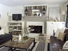 Love rustic panel above mantel and rustic coffee table with white bookshelves on either side of fireplace