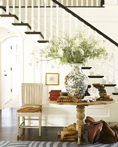 Rustic pedestal table, oversized vase, small scale art, white staircase with black bannister and treads - Savvy Home: Beauty in the Details: A Beach Cottage with Patina