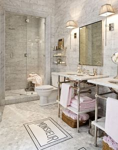 Designer Betty Lou Phillips' marble bathroom. The bath mats were inspired by a pair of vintage French napkin rings marked Monsieur and Madame.