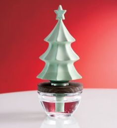 """Scents Of Ambiance™ Christmas Tree  Item #:  D925  This porcelain evergreen tree topper is our own patented technology. The wick releases continual fragrance from the clear glass base. Handsome wood collar rests just below the tree for added charm. Add your favourite fragranced oil and enjoy! 7 3/4"""" (18 cm) h, 3 1/2"""" (8 cm) dia. Fragranced Oil sold separately.  Regular Price (CDN):  $35.00 each ~ Outlet Sale Price (CDN):  $12.00 each ~ While supplies last!"""
