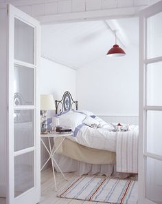 Pale blue and deep red are used as accents in this white-dominated room; blond floorboards & a linen sheet add a modicum of warmth. (England)