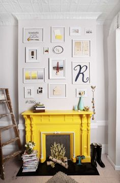 love this fireplace painted bright yellow and the gallery wall above it.