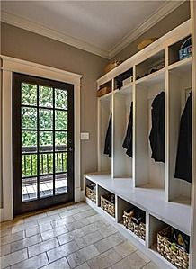 This mud room has open storage spaces. Door has glass on it to come light through. We can see is cabinet. Extra baskets for storage are there. We can see rectangle shape on shelf and basket. Light colour wooden floor with vertical and horizontal lines.