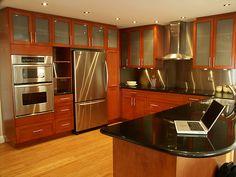 Modern red kitchen with wooden flooring