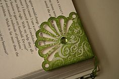 "Bookmark:  Cut 3"" strip & punch with Martha Stewart punch; cut down strip to 1 3/4"" from bottom of fan; fold edges up on back to make corner; put charm in; glue down overlapping papers on the back.    ETA: also been inked with distress ink when it was done."