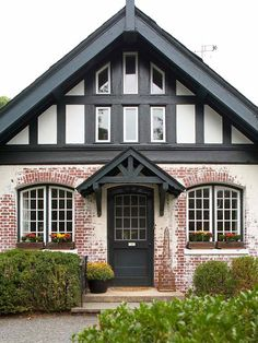 Black awnings provide pretty contrast to this cottage home. roof, the doors, awning front porch, front entrances, black brick exterior, front door cottage black, front entry, cottage front doors, cottage homes