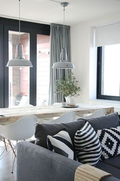 Grey couch, striped pillows, dining table, white chairs