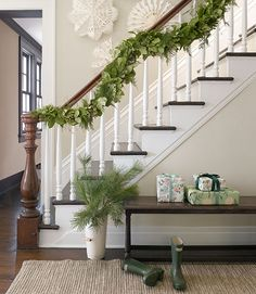 Christmas in a Sophisticated Connecticut Farmhouse.  Mixed greenery garland, paper snowflakes from Cultural Intrigue.  Off-white wall paint by Farrow & Ball.