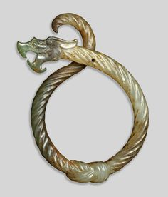 Jade Serpentine Dragon Pendant, this pendant makes hard jade appear impossibly supple and pliant as a twisted rope knotted at the bottom, 3rd century BC. Eastern Zhou dynasty (770–256 BC) China.