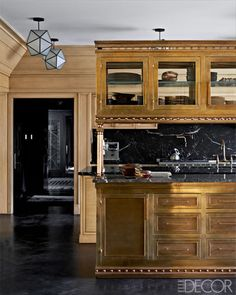 The island in the kitchen is brass, the cabinetry is cerused oak, and the countertops are marble.