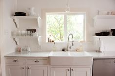 Our remodeled kitchen with white Shaker cabinets, open shelving, and farmhouse sink
