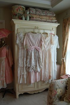 antique dresses displayed on an armoire