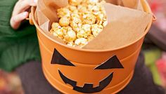 Turn a plain bucket into a multipurpose jack-o'-lantern that holds snacks or goes trick-or-treating.