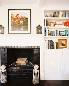 Living Room - A built-in bookcase beside a white mantel decorated with art and a pair of sconces