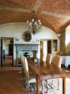 Spectacular dining room with farmhouse table and brick ceiling.