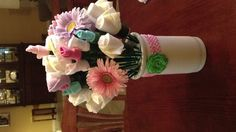 Diaper and baby sock flower arrangement with a headband and flower hair clip.
