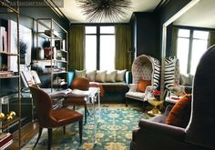 Amy D. Morris Interiors - black turquoise blue green eclectic modern den office design with green silk curtains, turquois eblue settee champagne silver silk pillows, acrylic lucite desk table, burnt orange leather chairs with nailhead trim, gold & turquoise blue rug, gold bookcases, black walls paint color, silver leaf beveled floor mirror and ivory & black domed tufted zebra chair.